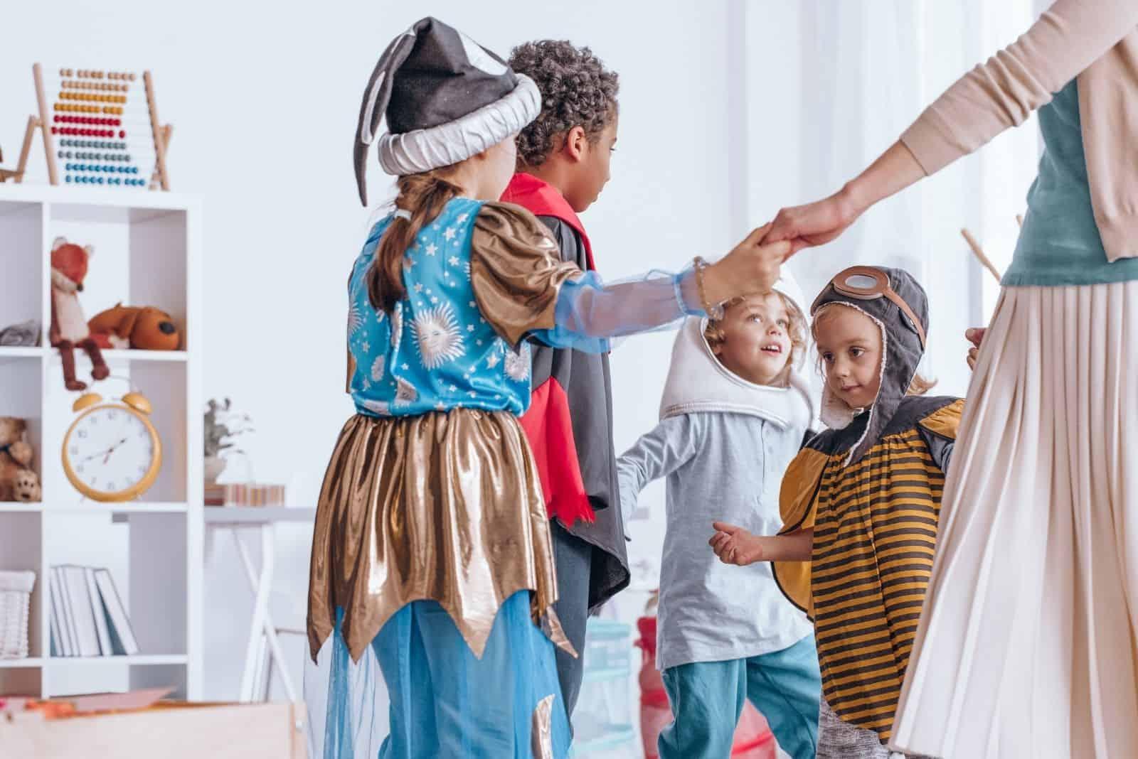 Kinder in Kostümen spielen und Händchen halten im Klassenzimmer