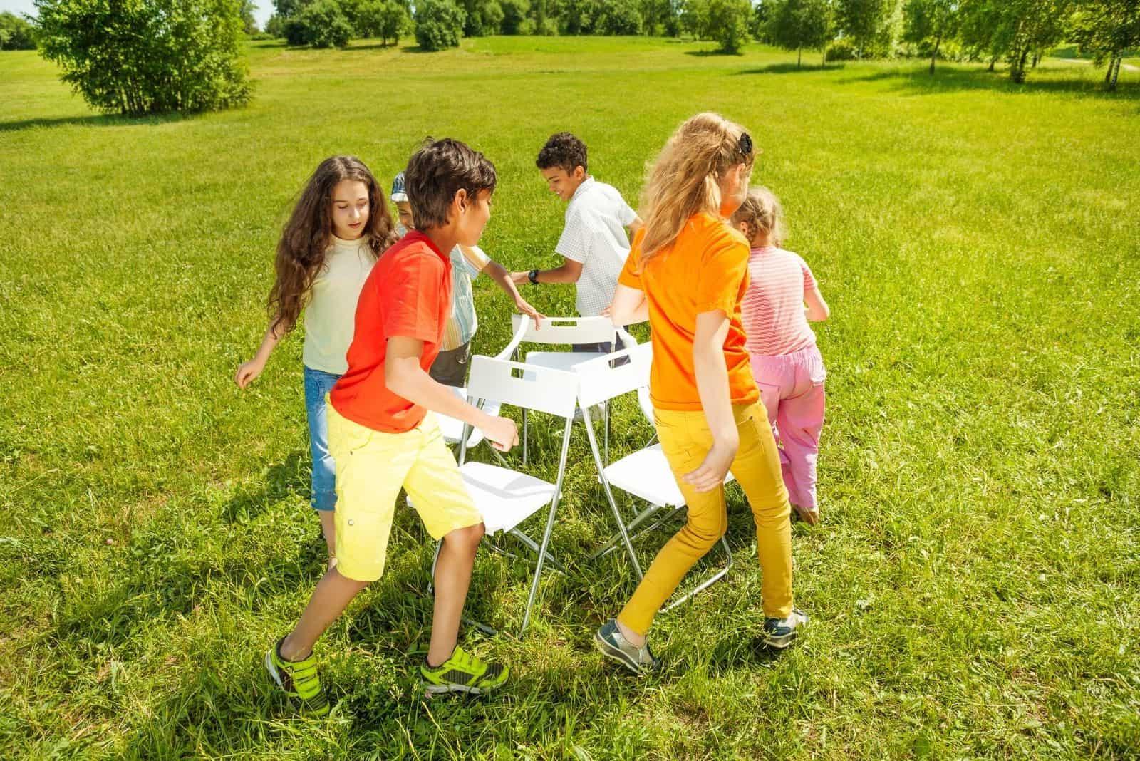 Kinder laufen um die Stühle herum Musikstuhl im Freien spielen