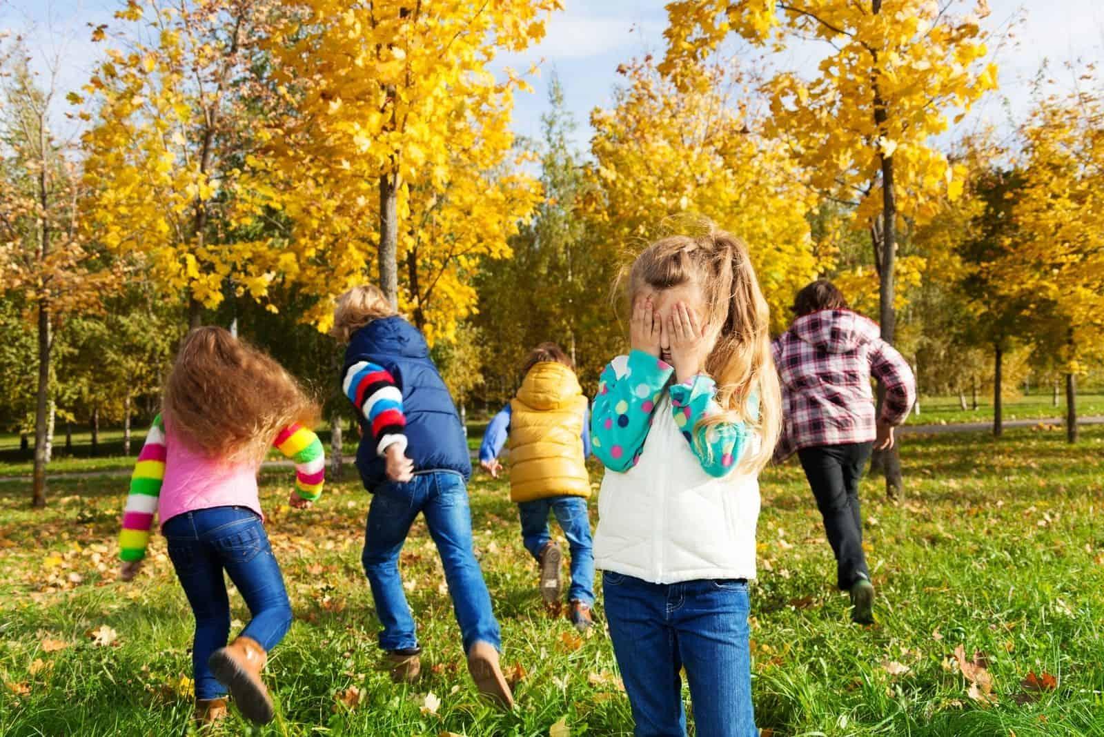 Kinder spielen Verstecken im Herbstpark