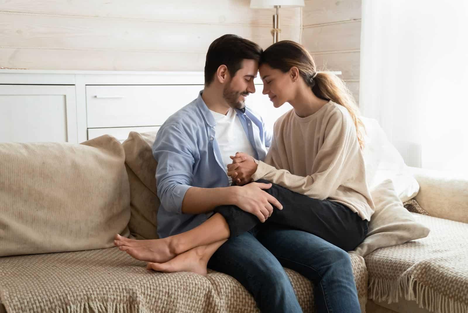 Liebevolles junges Ehepaar auf der Couch im Wohnzimmer sitzen und kuscheln kuscheln zärtlich süßen Moment zusammen genießen