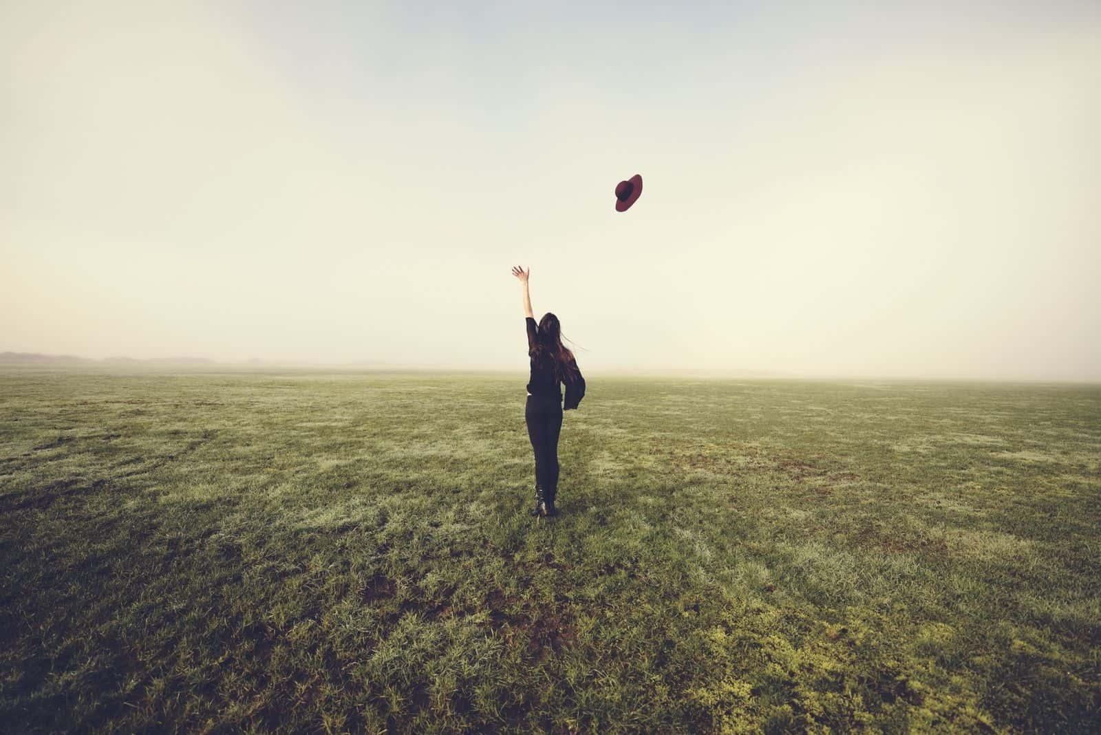 Loslassen Konzept einer Frau, die Hut in die Luft wirft