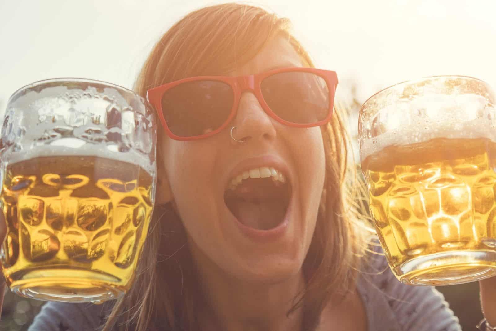 Mädchen trinkt Bier Sonnenbrille tragen und zwei Bier in der Hand halten