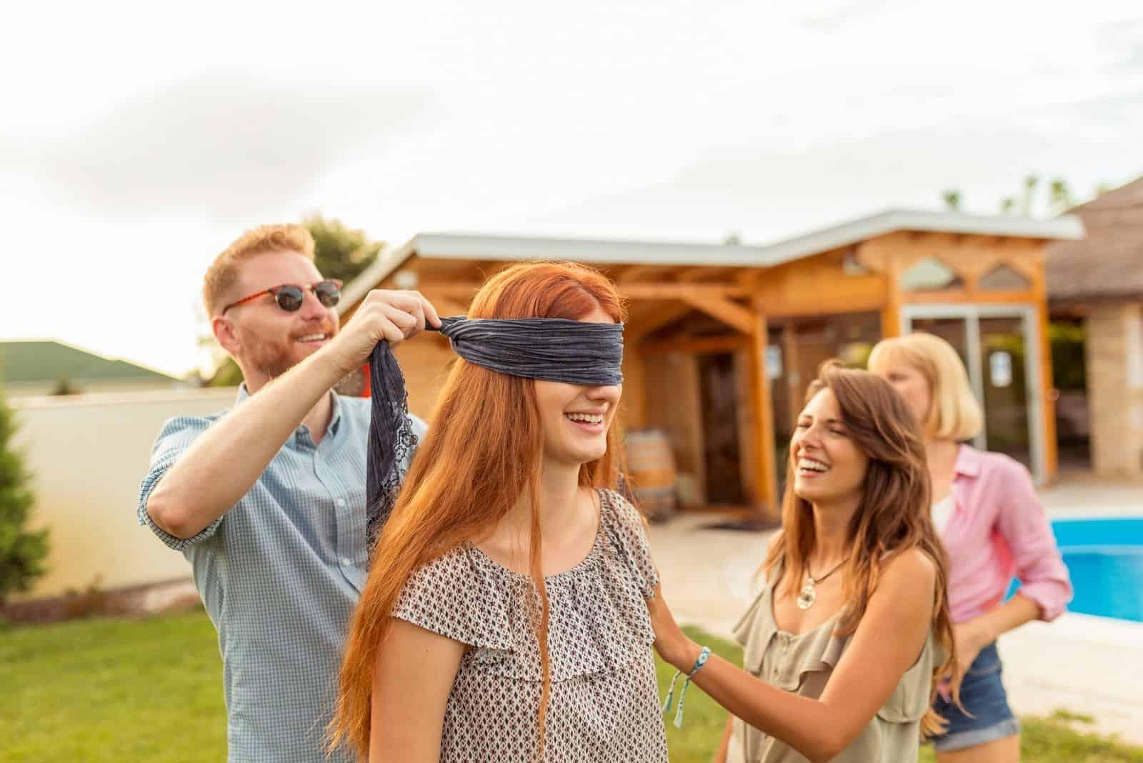 Mann verbindet einem Mädchen die Augen in der Nähe des Pools mit ein paar Freunden