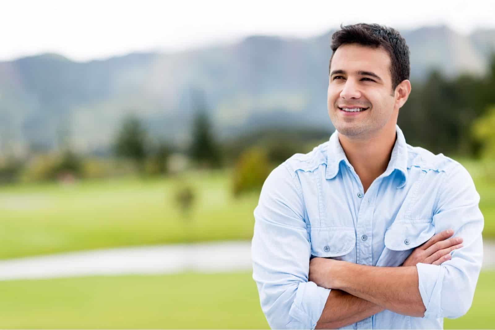 Nachdenklicher lässiger Mann draußen aufschauen und lächeln