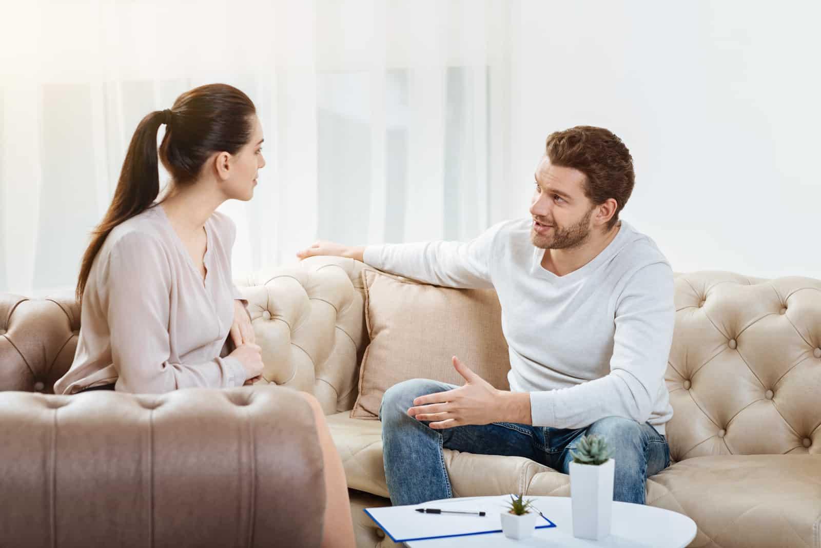 Paar sitzt im Wohnzimmer und redet