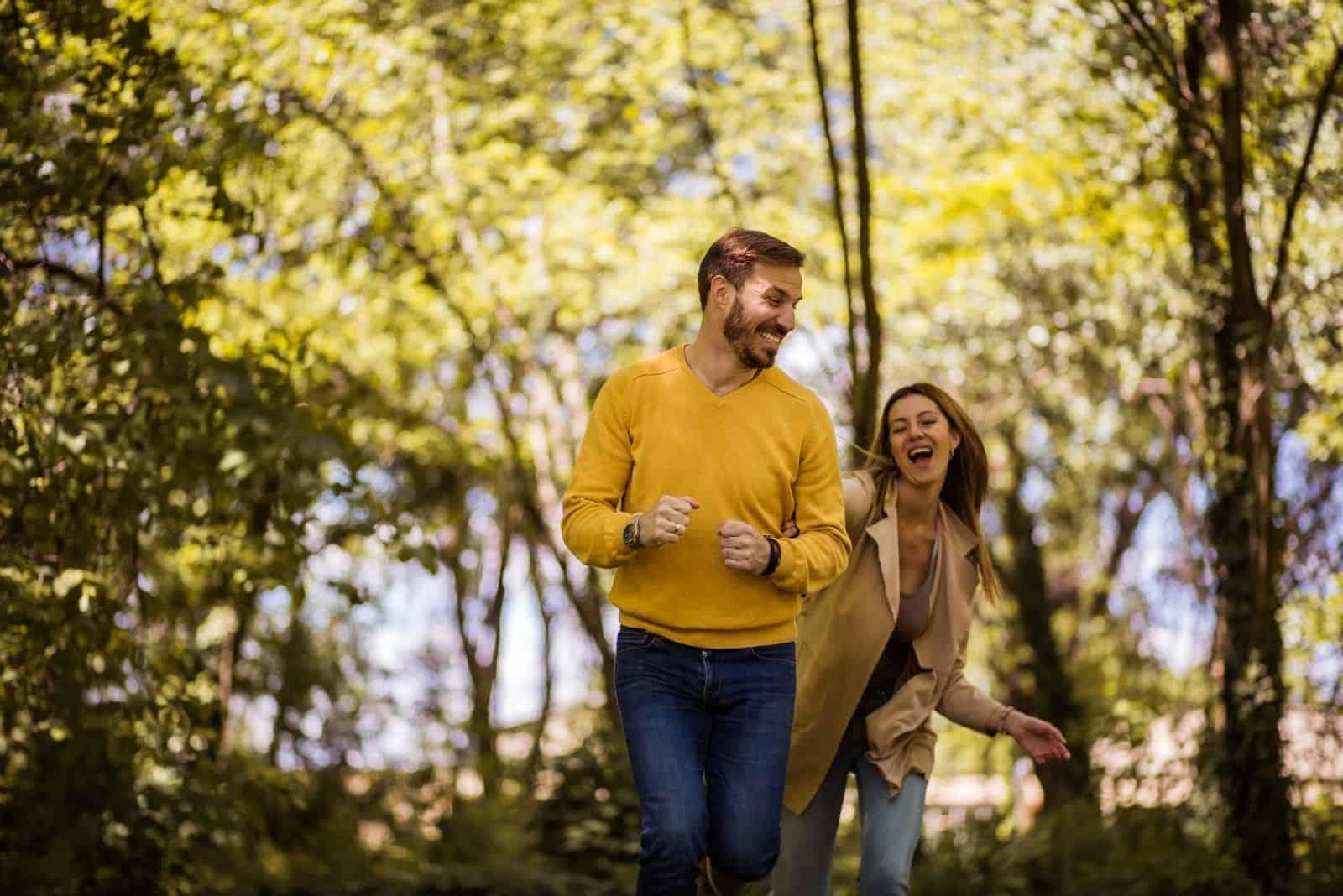 Paar spielt in der Natur mit der Frau, die auf den Mann tippt