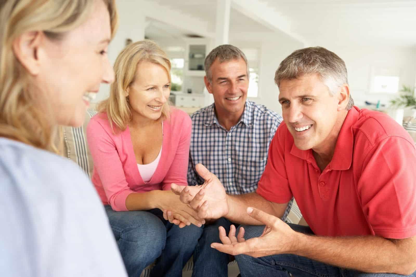 Paare mittleren Alters im Wohnzimmer reden