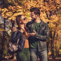 ein lächelnder Mann und eine Frau, die durch den Park gehen