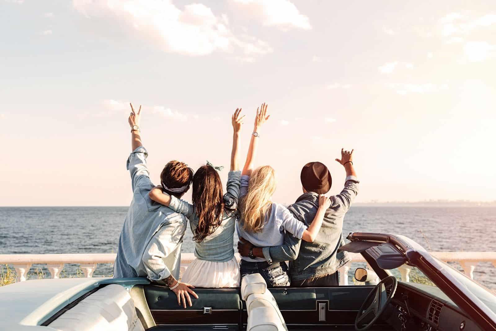 Rückansicht glücklicher junger Freunde mit erhobenen Händen neben dem Auto stehen