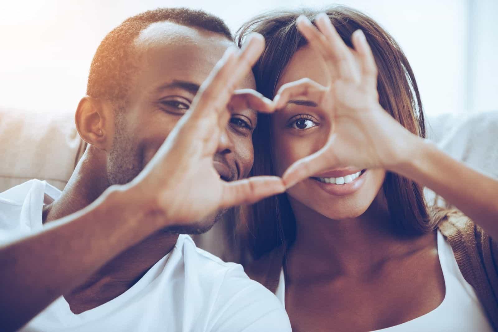 Schönes junges afrikanisches Paar sitzen dicht beieinander und schauen durch eine mit den Fingern gemachte Herzform