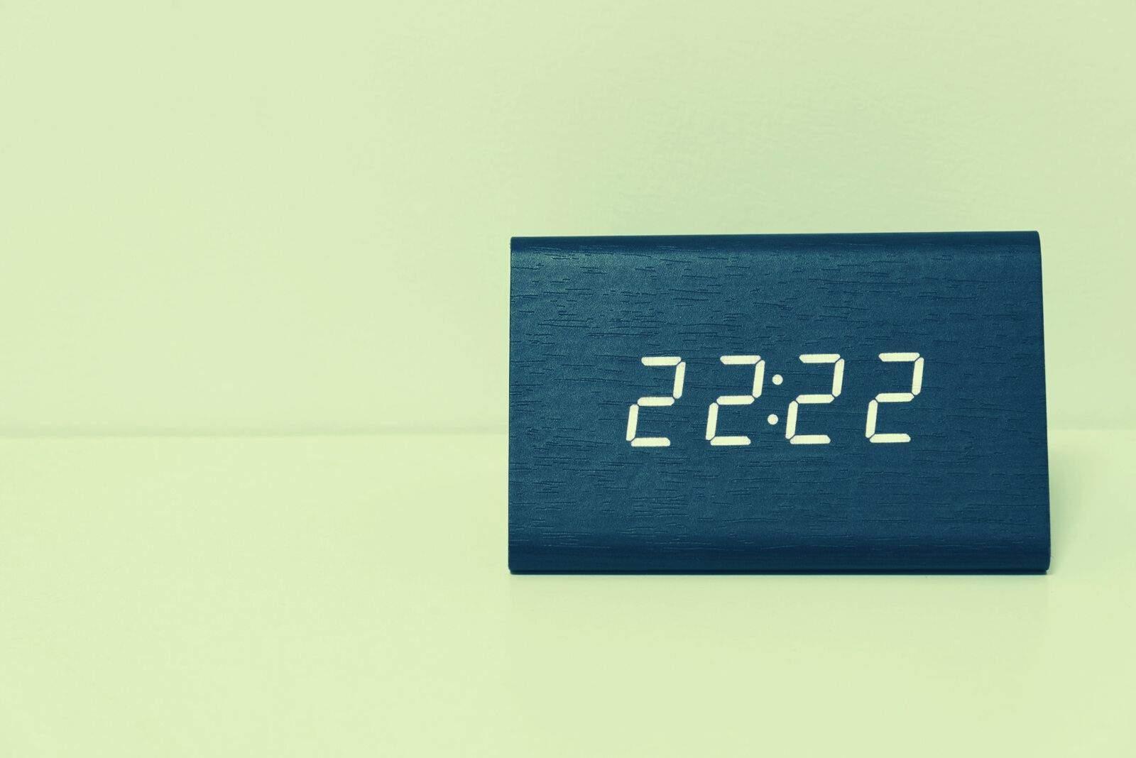 Schwarze Digitaluhr auf weißem Hintergrund mit Zeit 22:22