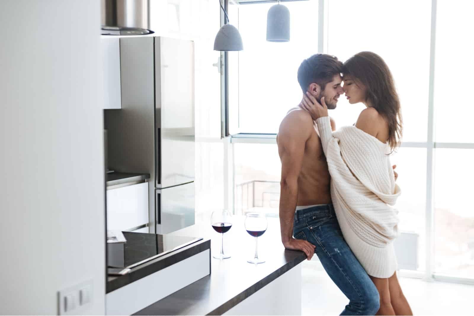 Sinnliches junges Paar steht und umarmt in der Küche