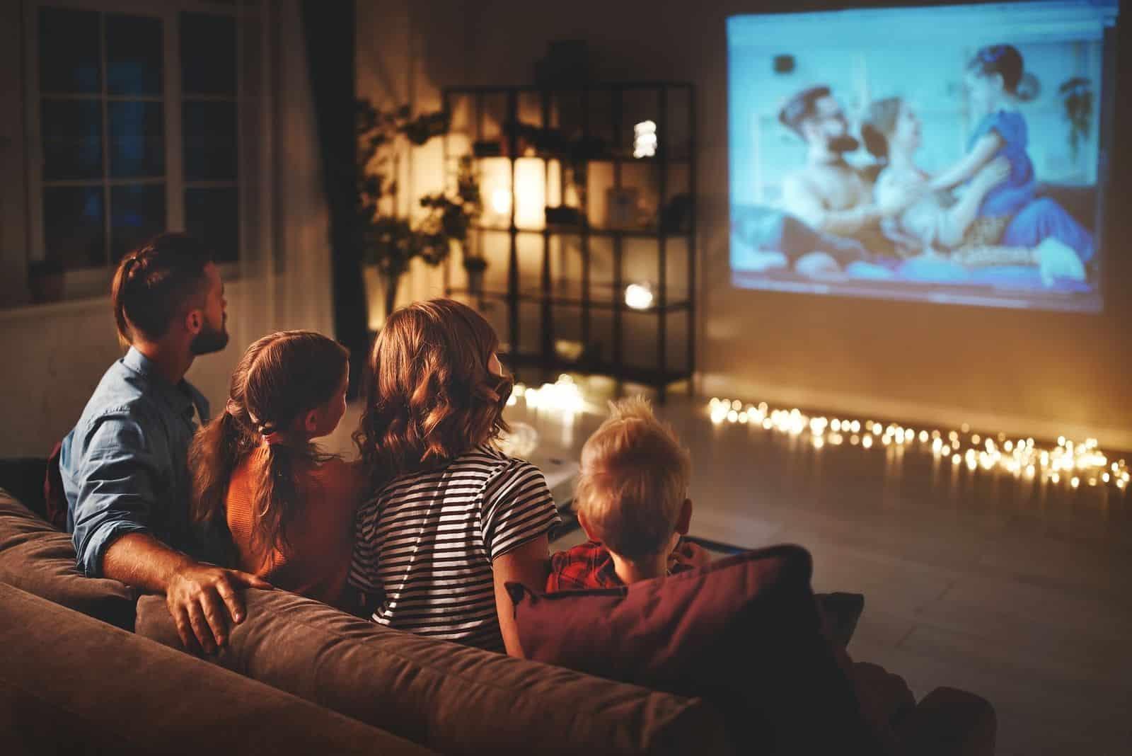 Vater und Mutter mit Kindern Nachts Filme über den Projektor im Wohnzimmer ansehen