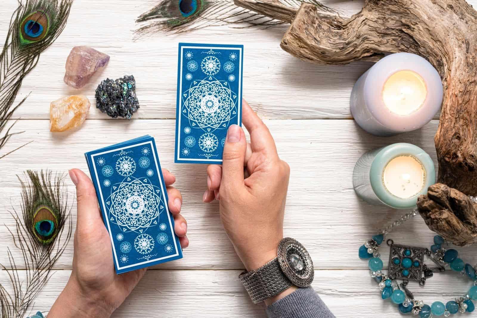 Wahrsagerin Frau und Karten eines blauen Tarot über weißem Holztischhintergrund.
