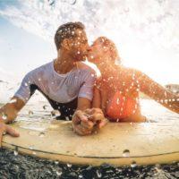 Glückliches sportliches Paar, das sich beim Surfen im Meer küsst