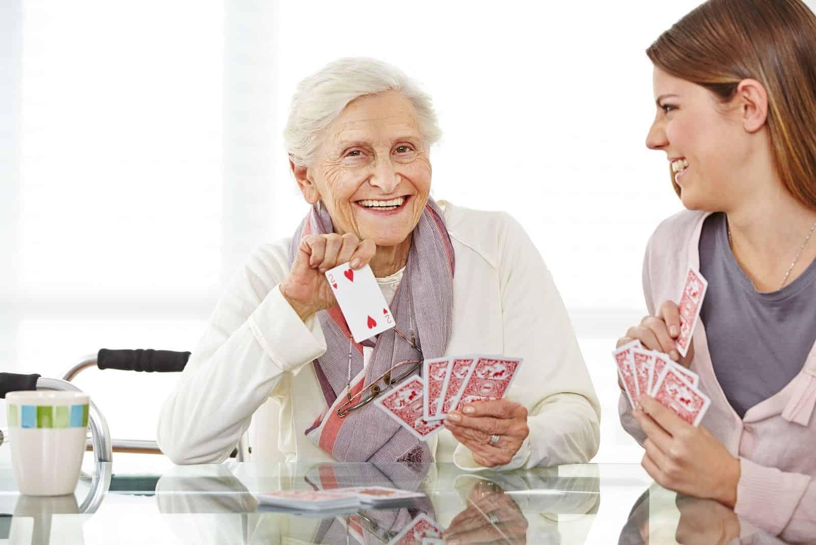 alte und junge frau Canasta spielen mit alter Frau, die Karte zeigt