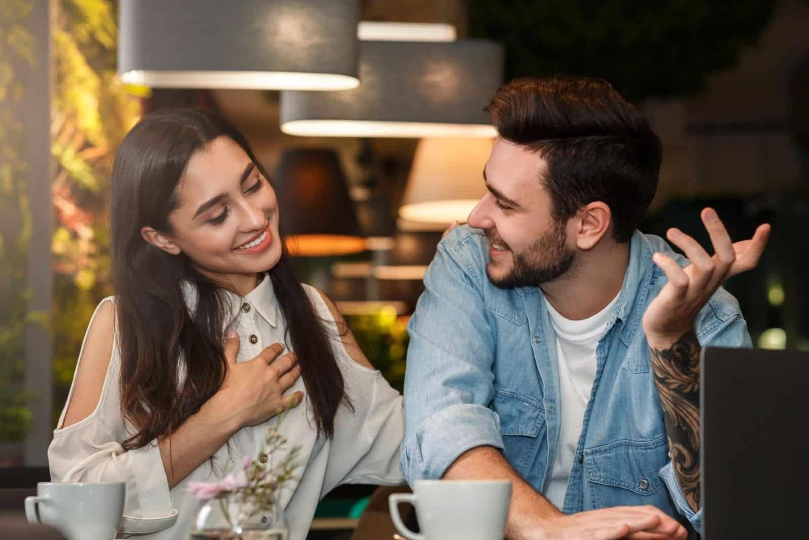 attraktives Mädchen flirtet über einen freiberuflichen Mann, der im Café arbeitet