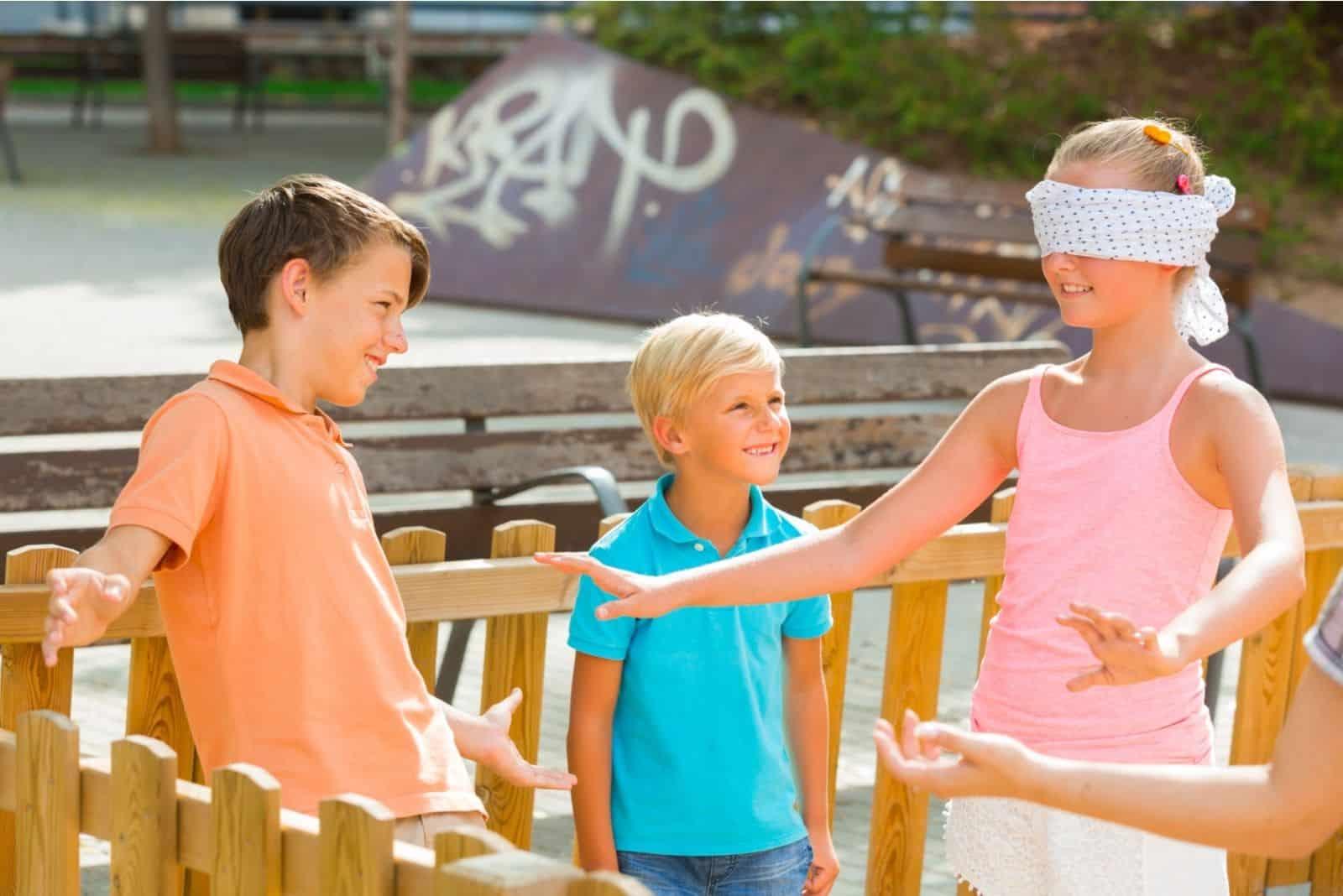 blinde Kuh, die von den Kindern gespielt wird in einem eingezäunten Außenbereich