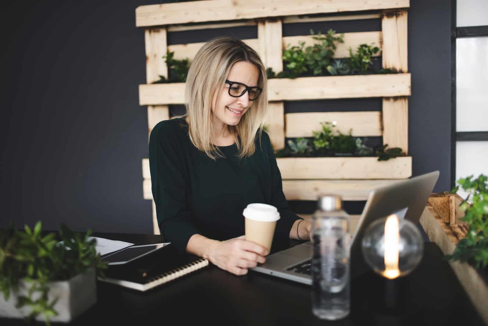 blonde Haare Frau sitzt und Knopf am Laptop
