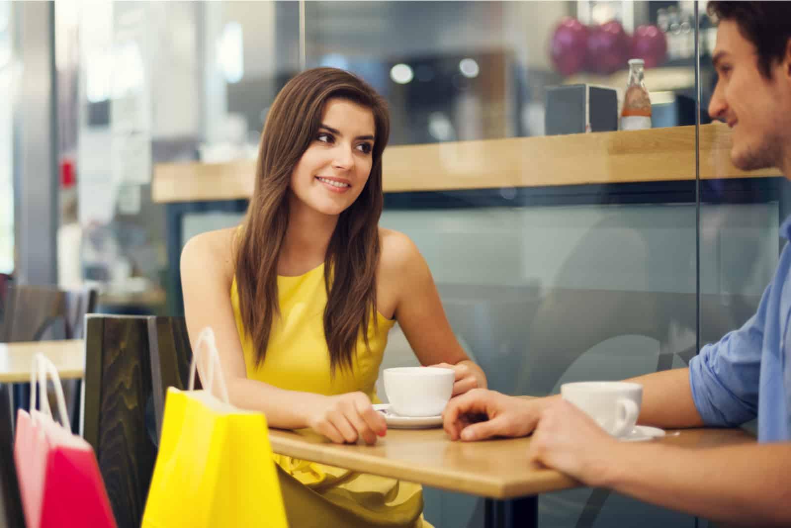 der mann sitzt sich gegenüber und trinkt kaffee