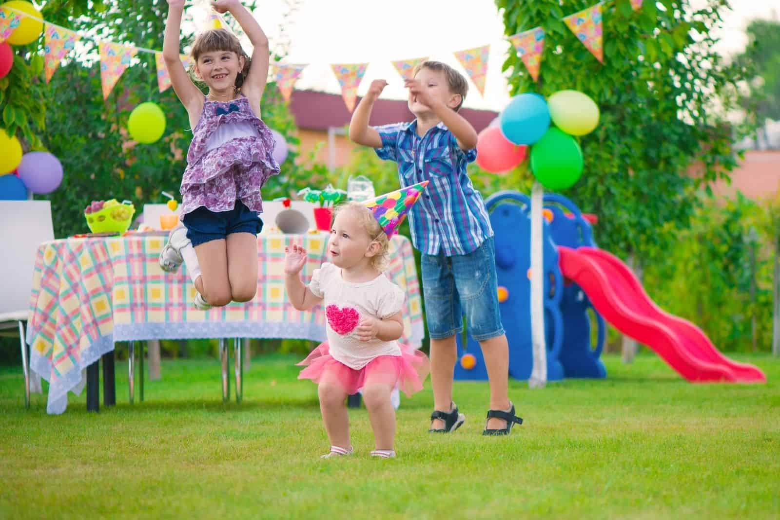 drei Kinder spielen auf der Party im Freien springen