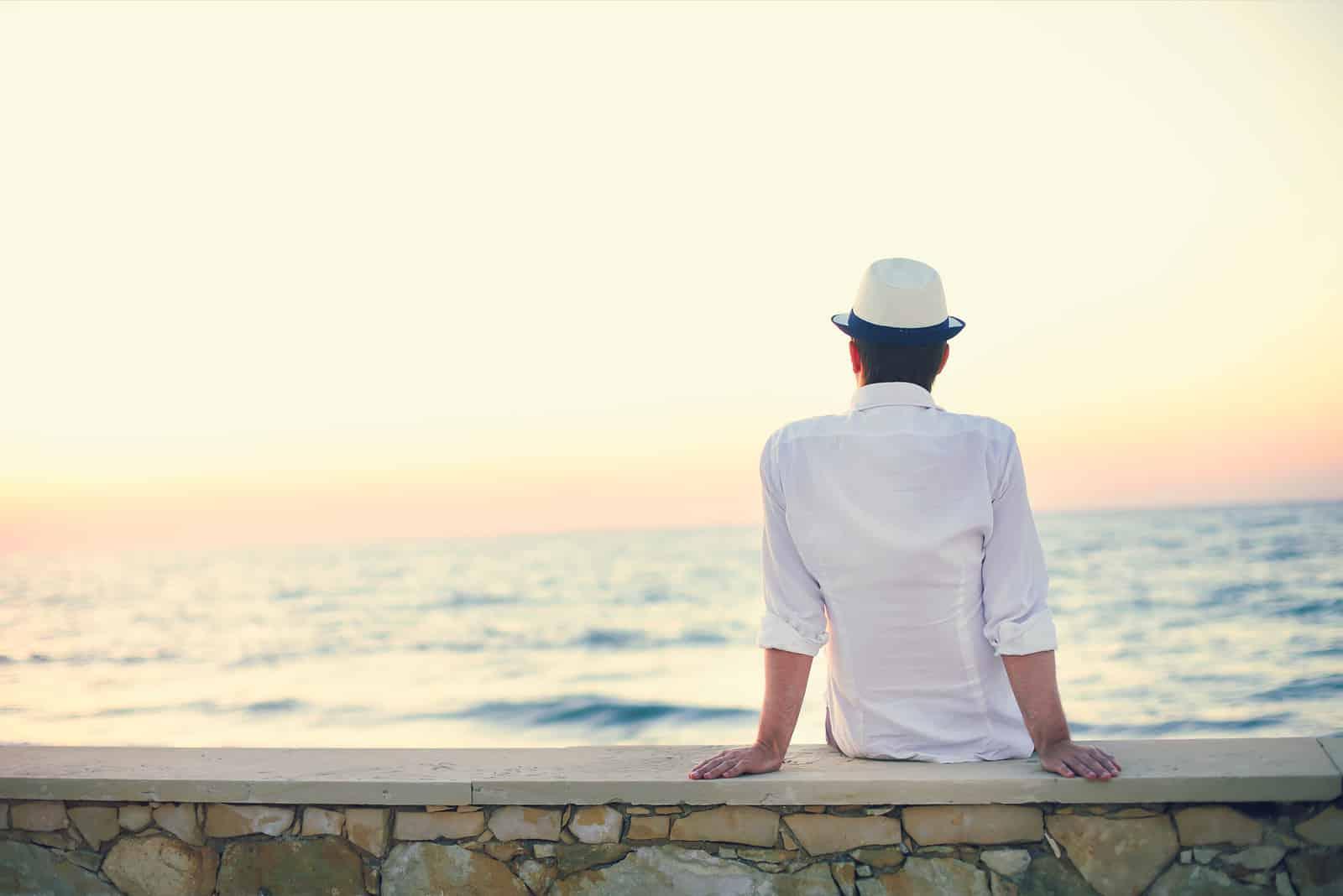 ein Mann mit Hut auf dem Kopf sitzt und schaut aufs Meer