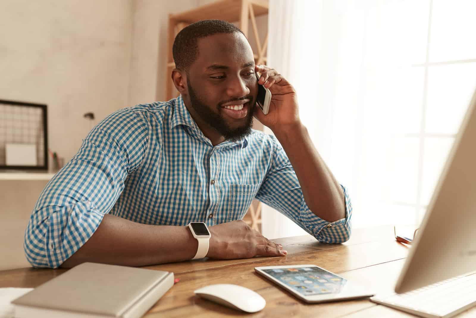 ein Mann sitzt an einem Tisch und telefoniert