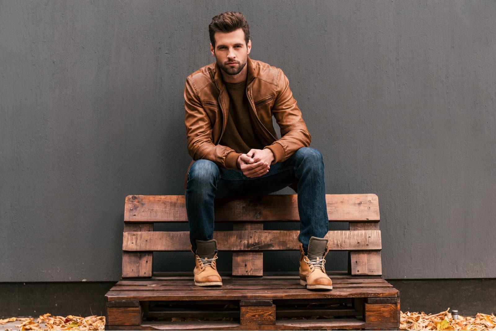 ein Mann sitzt auf einer Holzbank