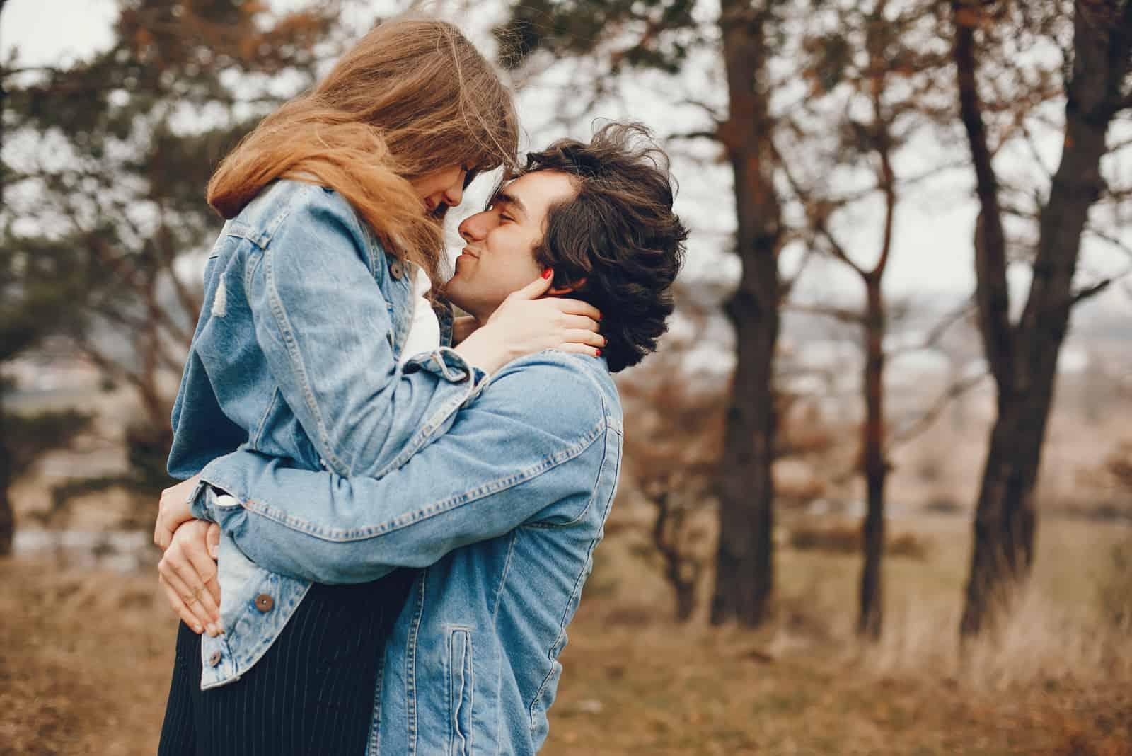 ein Mann umarmt eine blonde Frau und trägt sie