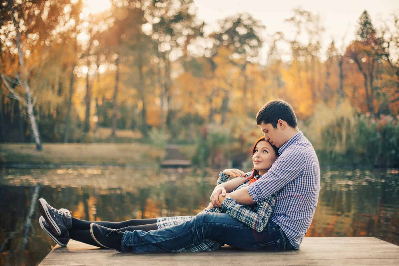 ein Mann und eine Frau sitzen sich umarmend auf einem Pier am Fluss