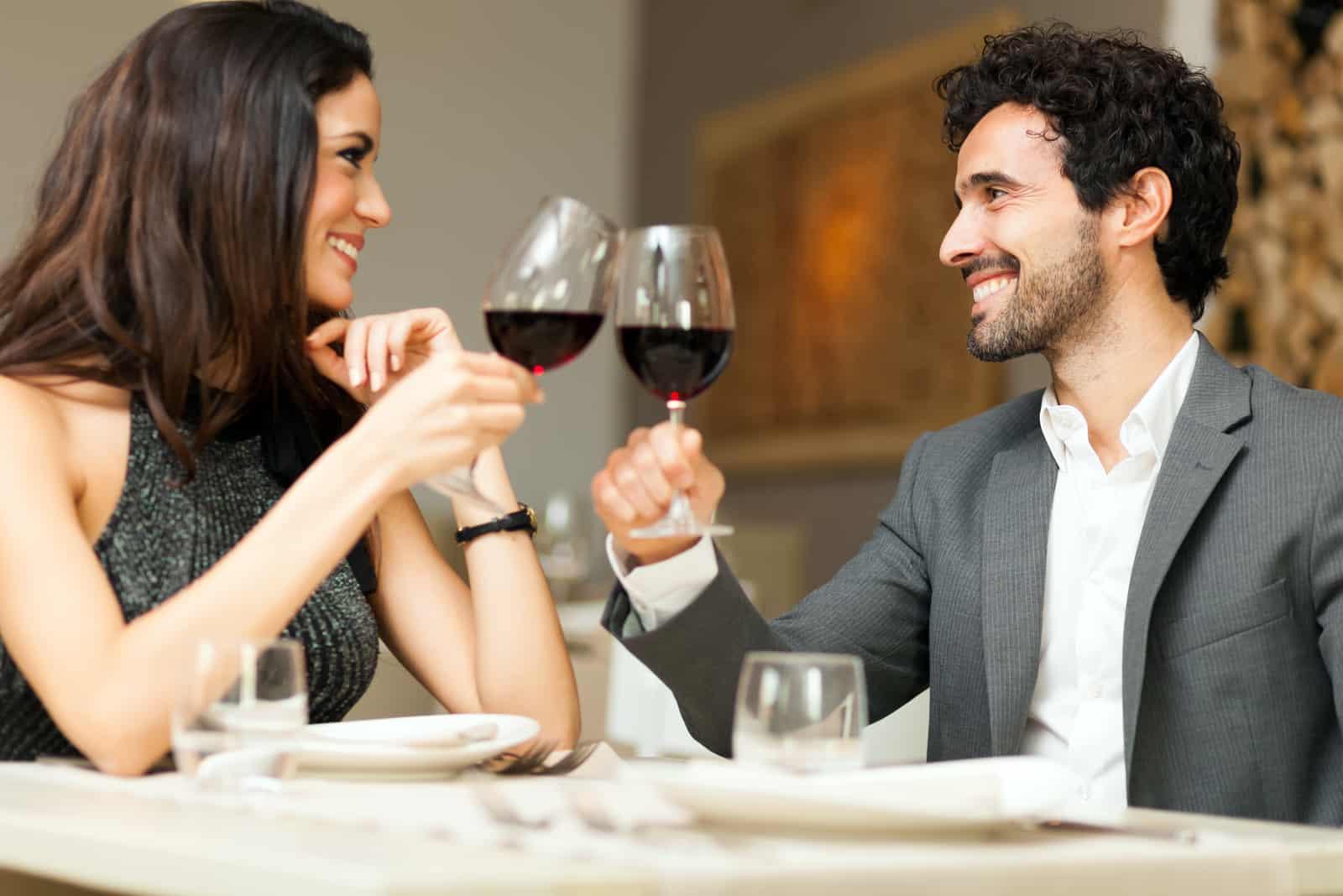 ein Mann und eine Frau stoßen mit Wein an