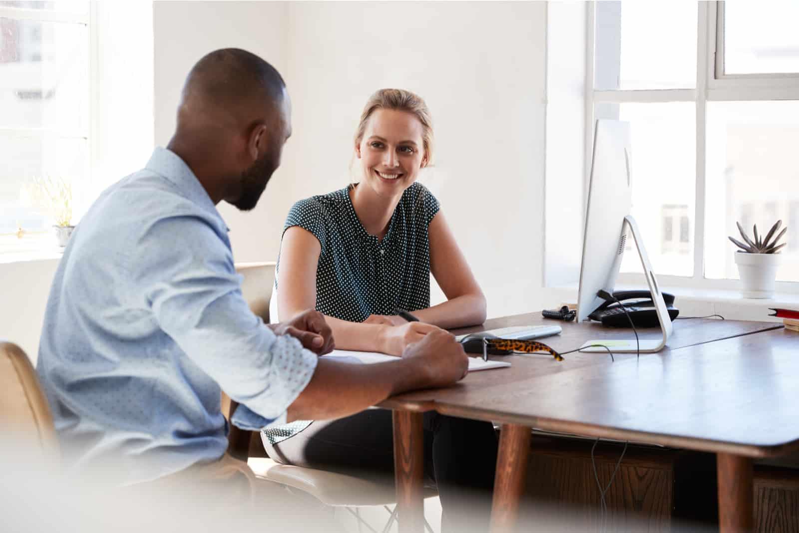 ein Mann und eine Frau unterhalten sich bei der Arbeit