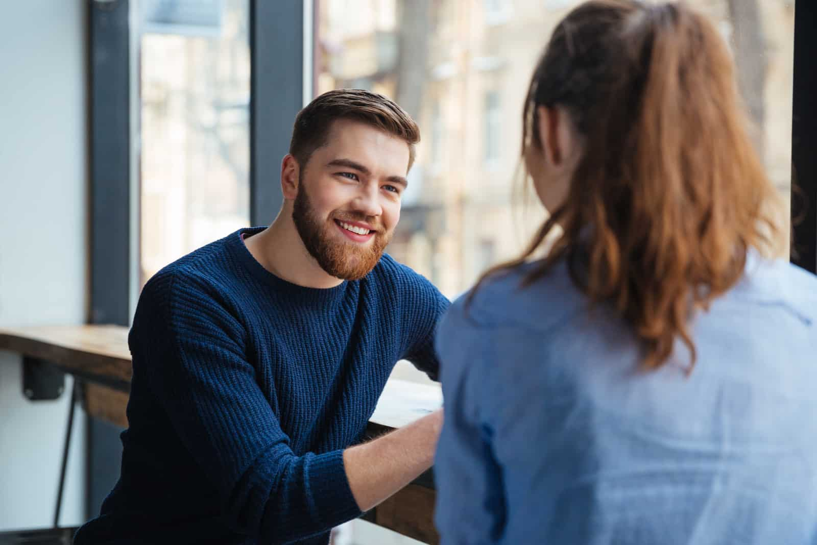 ein lächelnder Mann, der mit einer Frau spricht