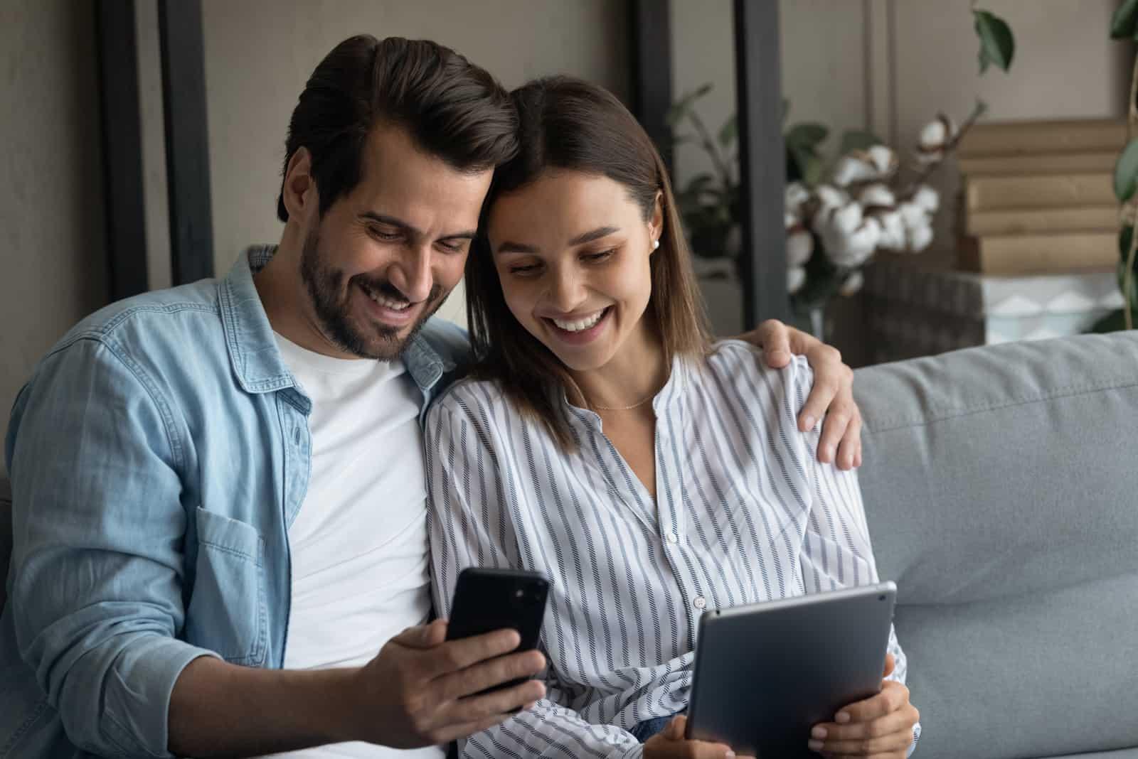 ein lächelnder mann und eine frau sitzen und schauen auf das tablet