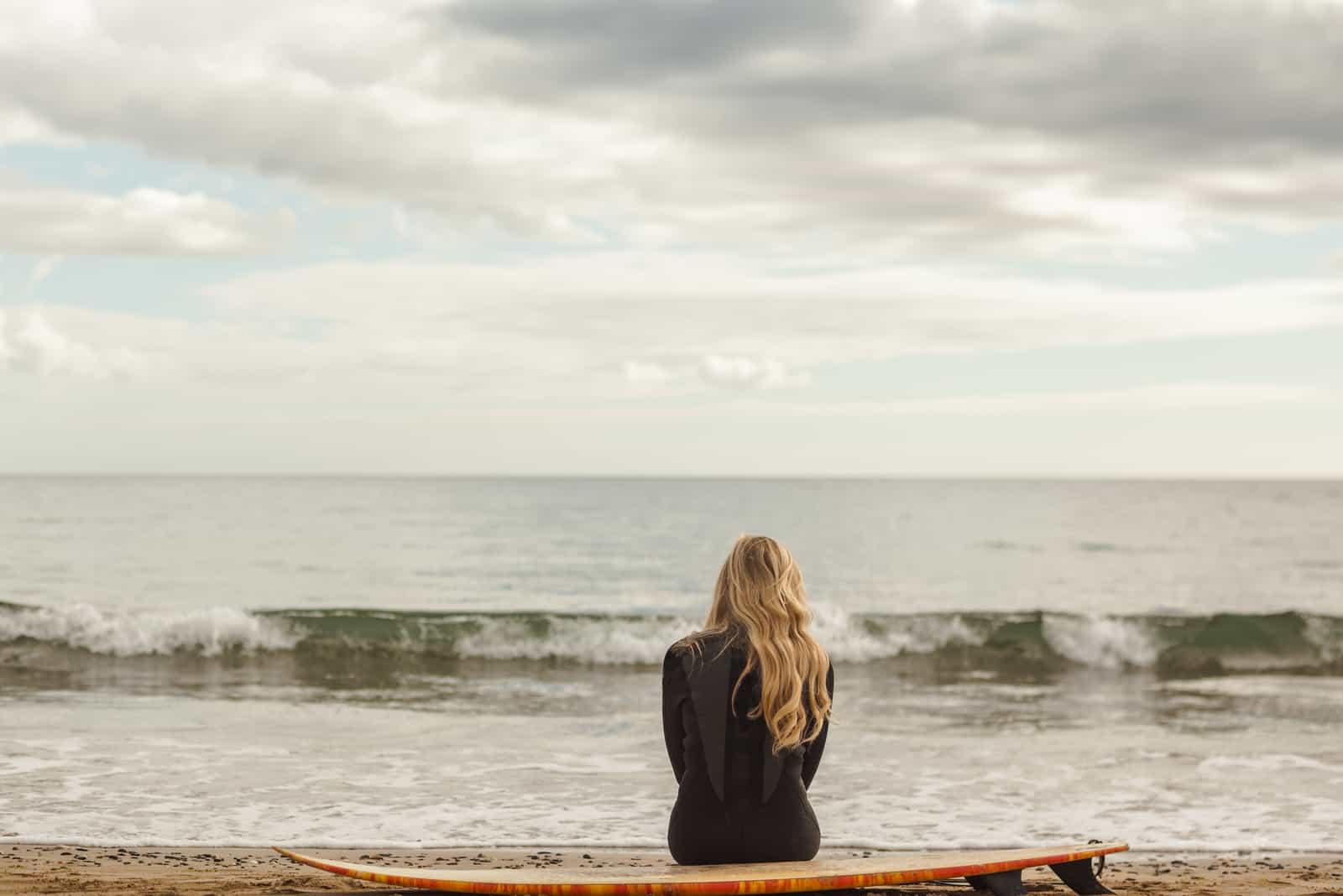 eine Frau mit langen blonden Haaren sitzt am Meer