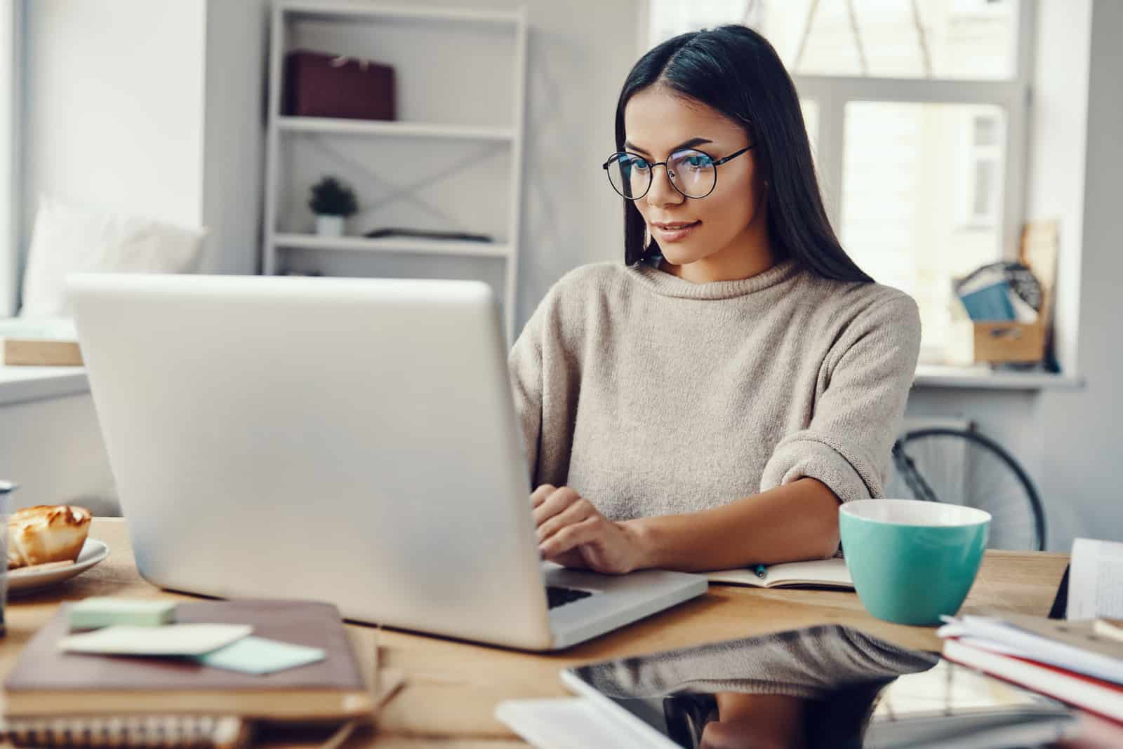 eine Frau mit langen schwarzen Haaren, die an einem Tisch sitzt und auf einem Laptop tippt