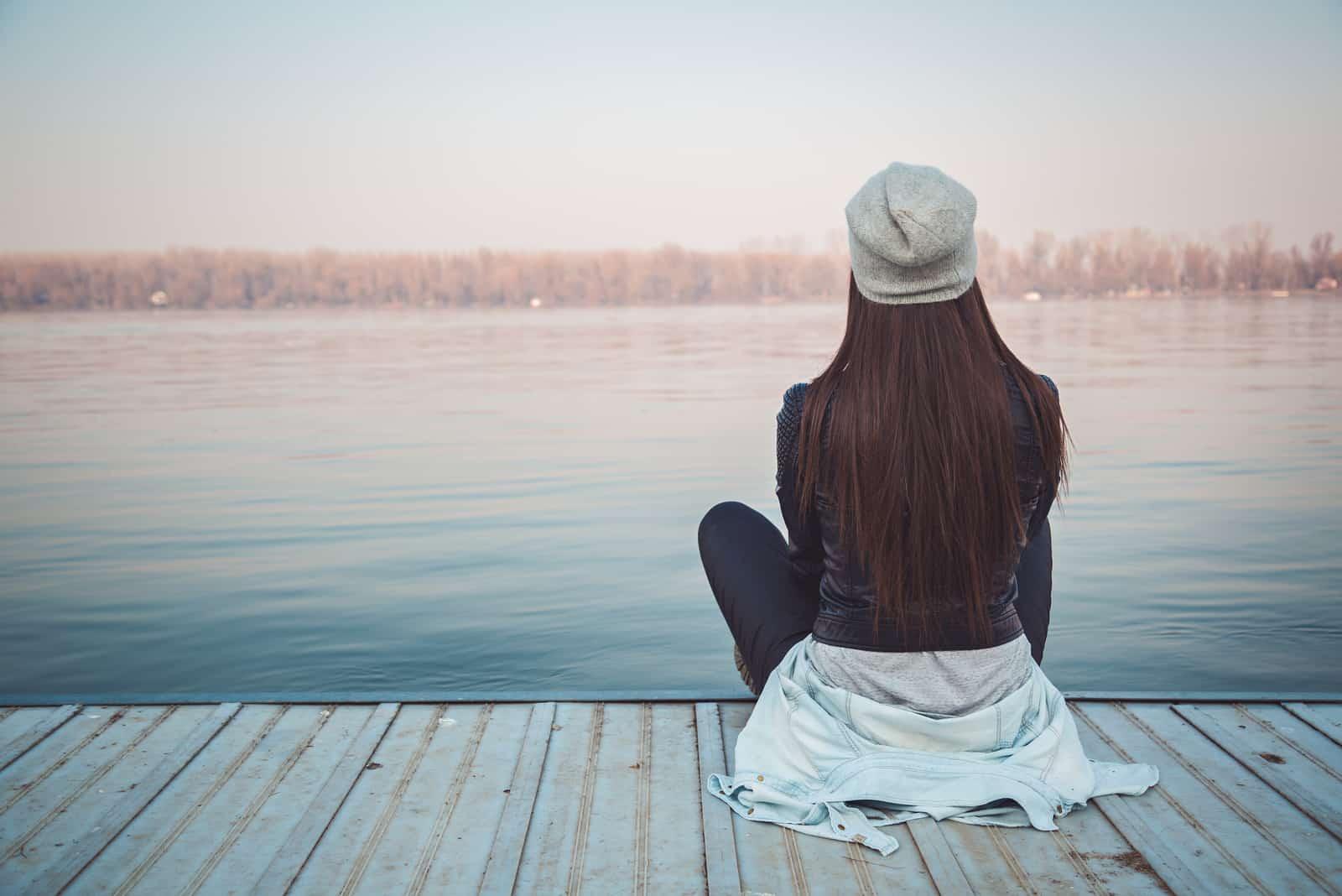 eine Frau mit langen schwarzen Haaren sitzt auf einem Pier