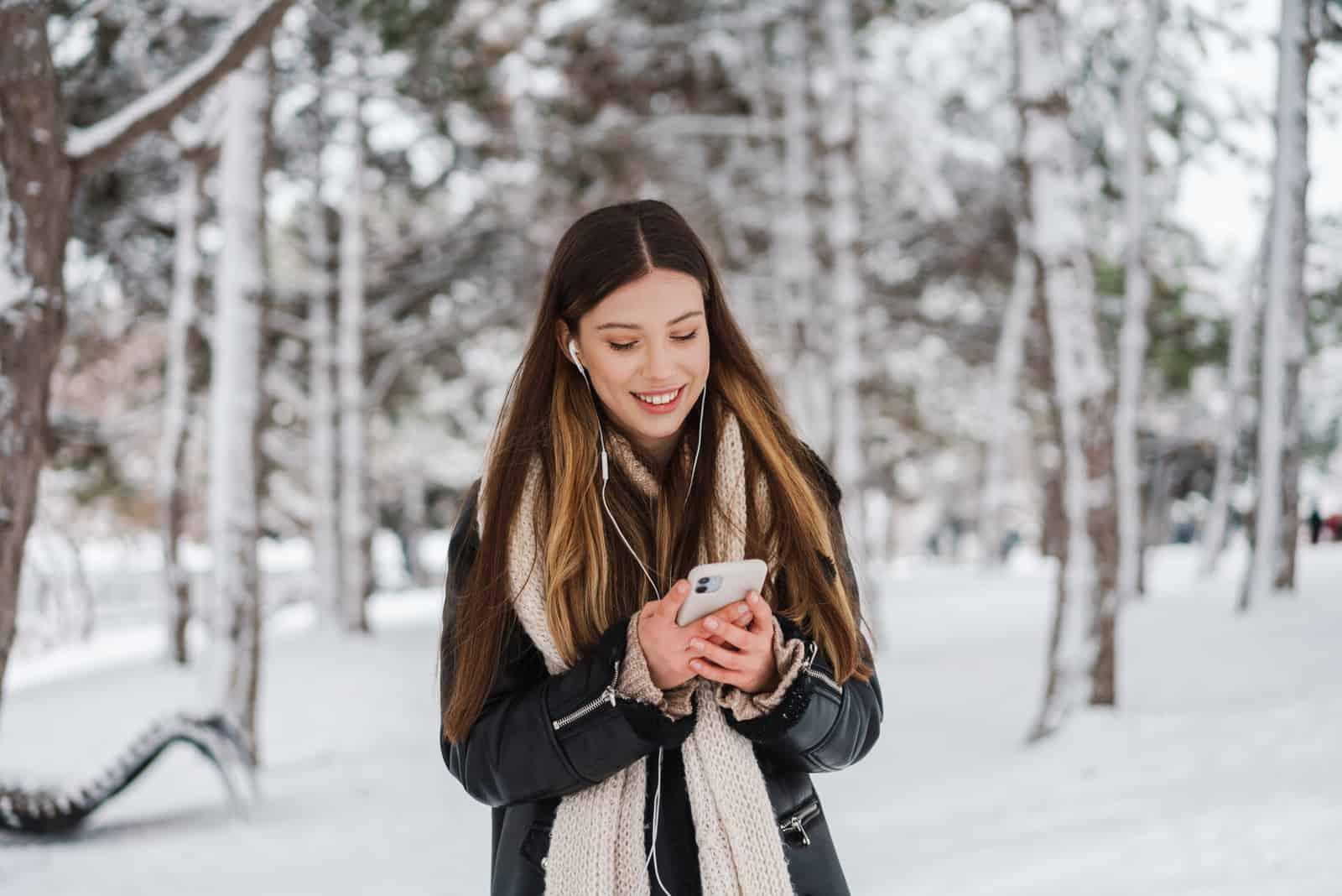 eine Frau steht im Schnee und ein Knopf am Telefon