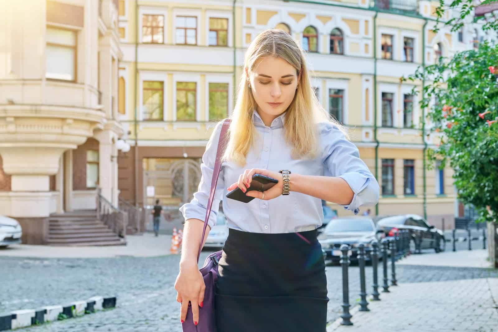 eine blonde Frau geht die Straße entlang und schaut auf ihre Uhr