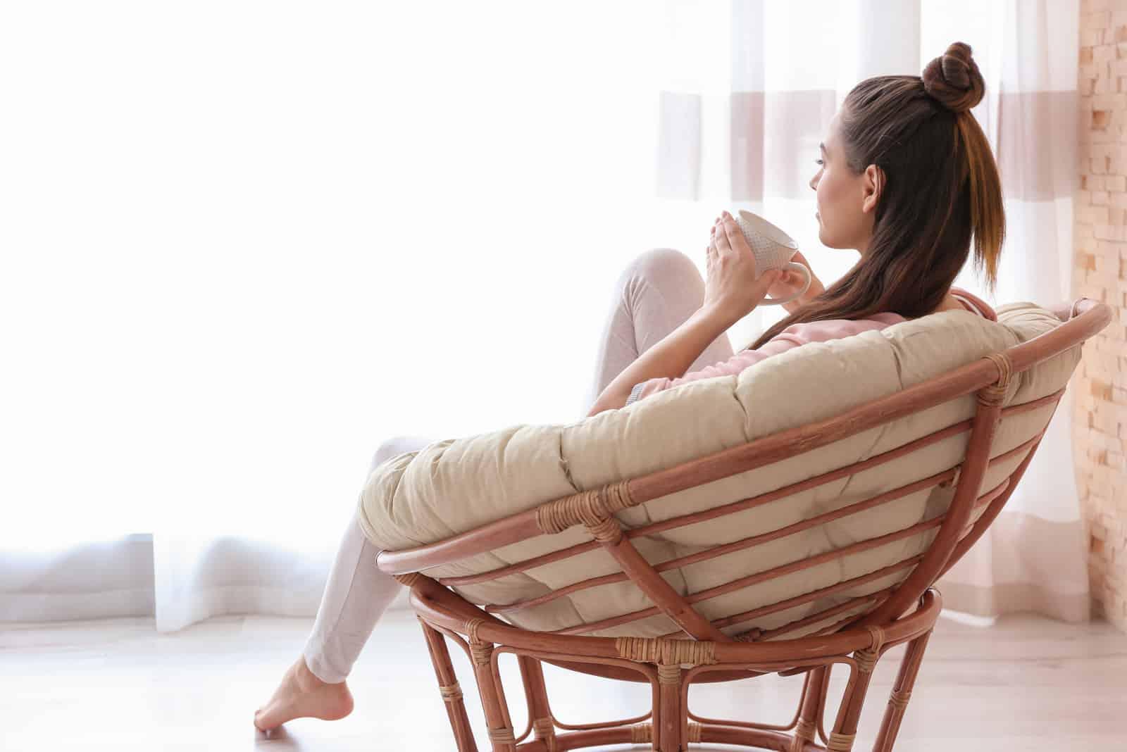 eine imaginäre Frau, die auf einem Stuhl sitzt und Kaffee trinkt und vor sich schaut