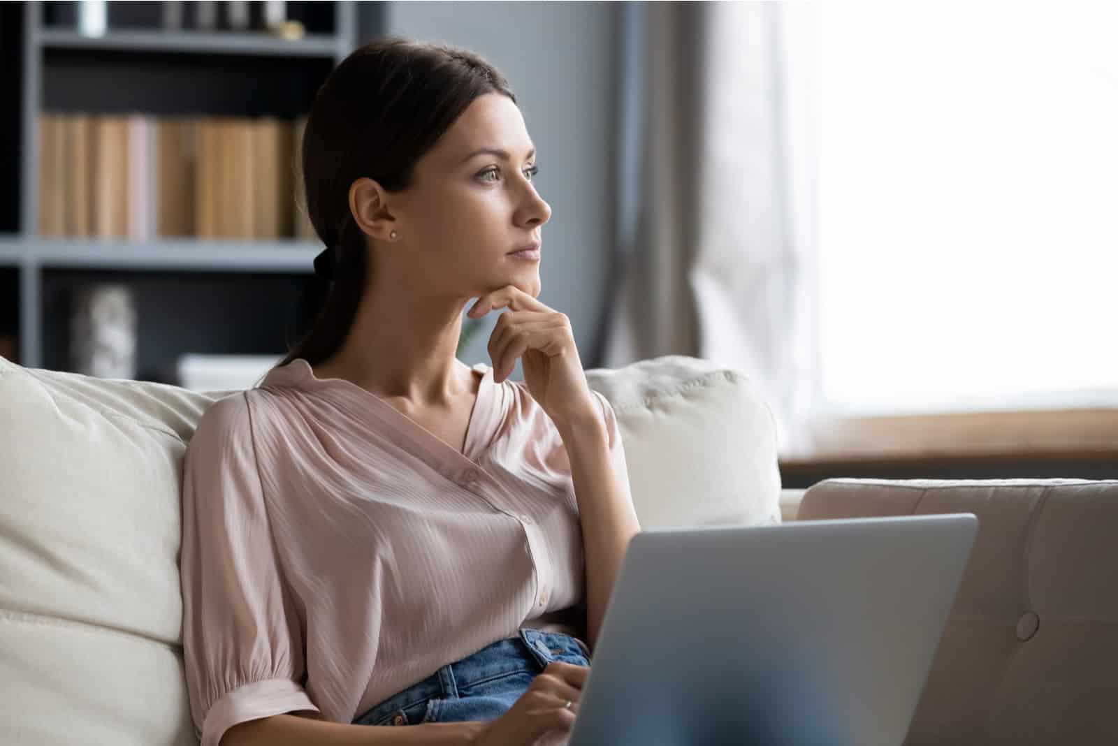eine imaginäre Frau, die hinter einem Laptop auf der Couch sitzt