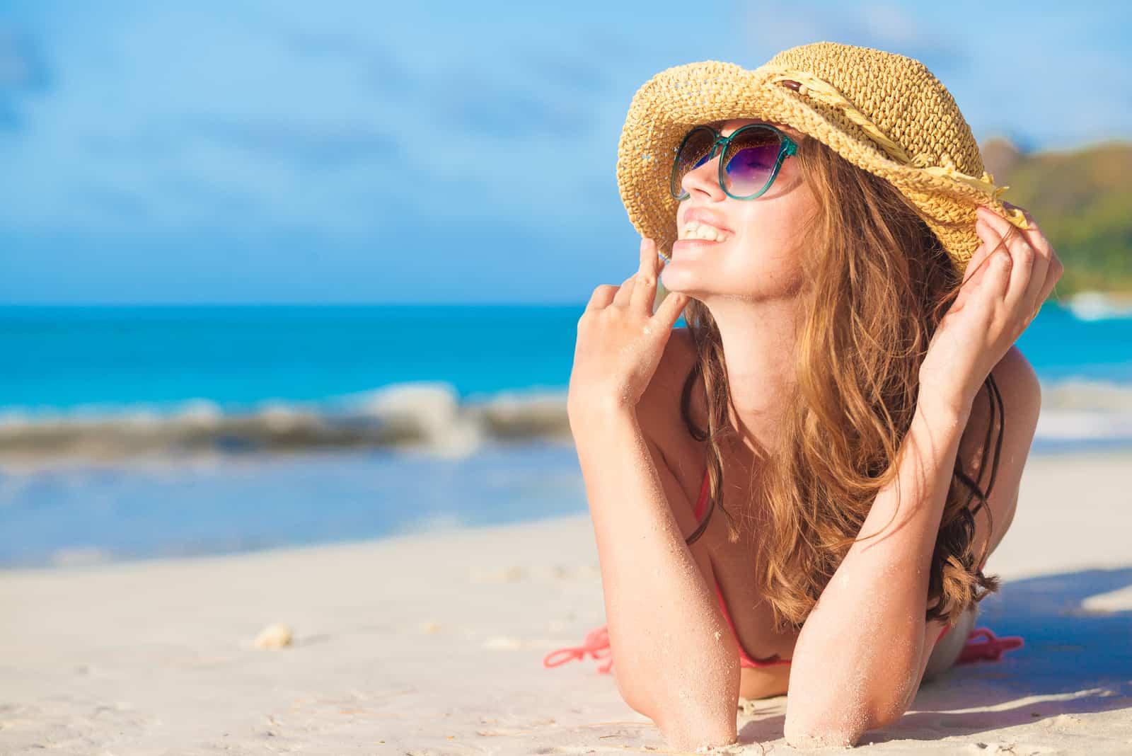 eine lächelnde Frau mit Hut auf dem Kopf liegt am Strand