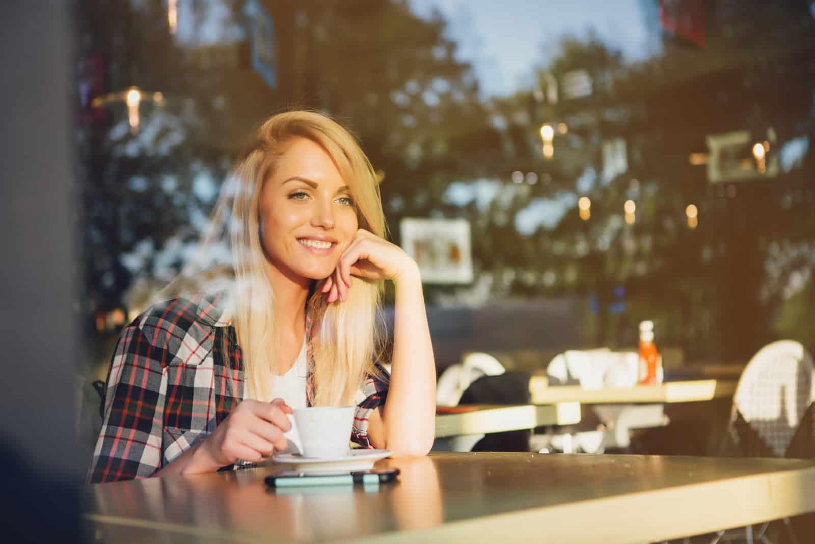 eine lächelnde blonde Frau, die Kaffee trinkt