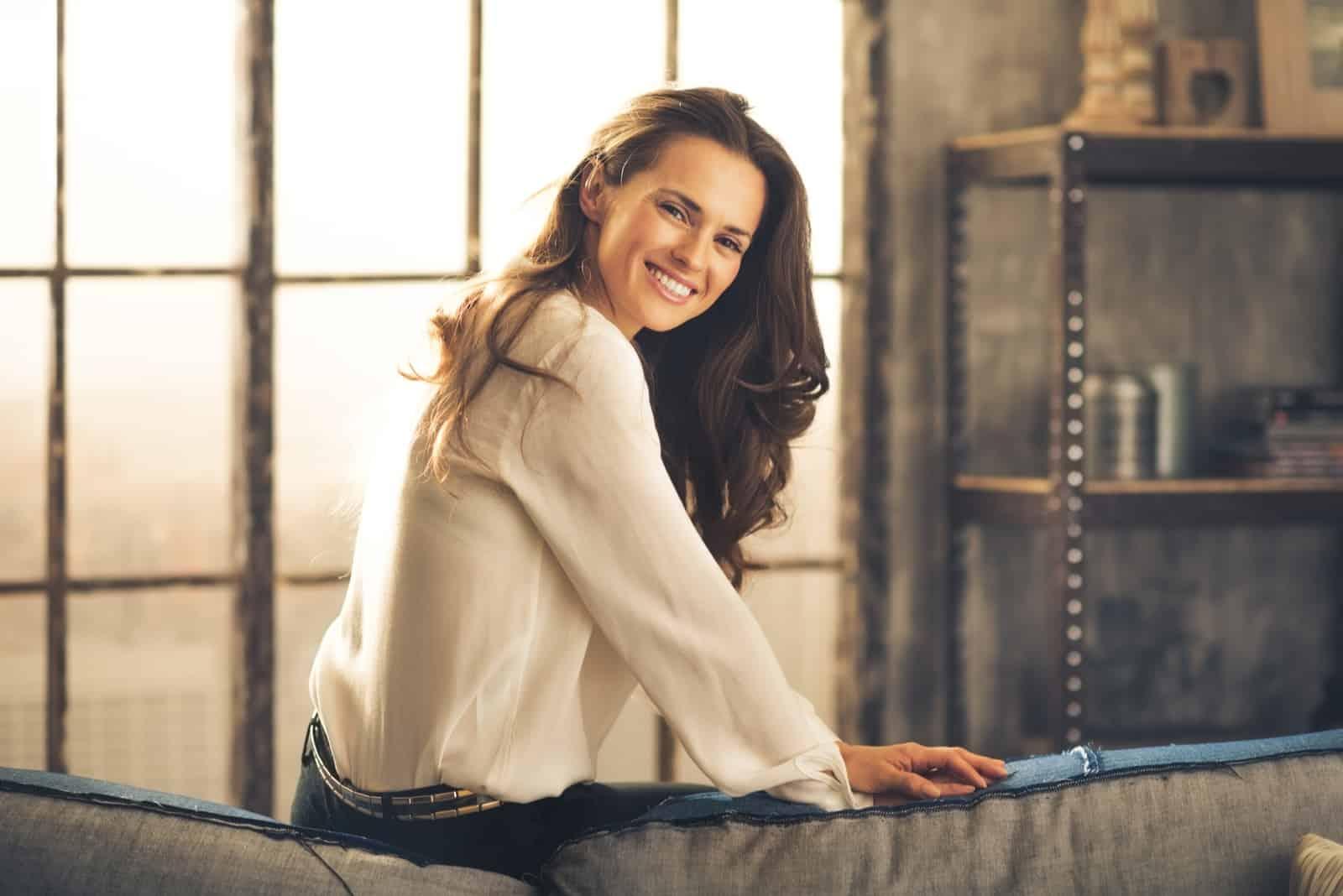eine lächelnde braunhaarige Frau sitzt auf der Couch