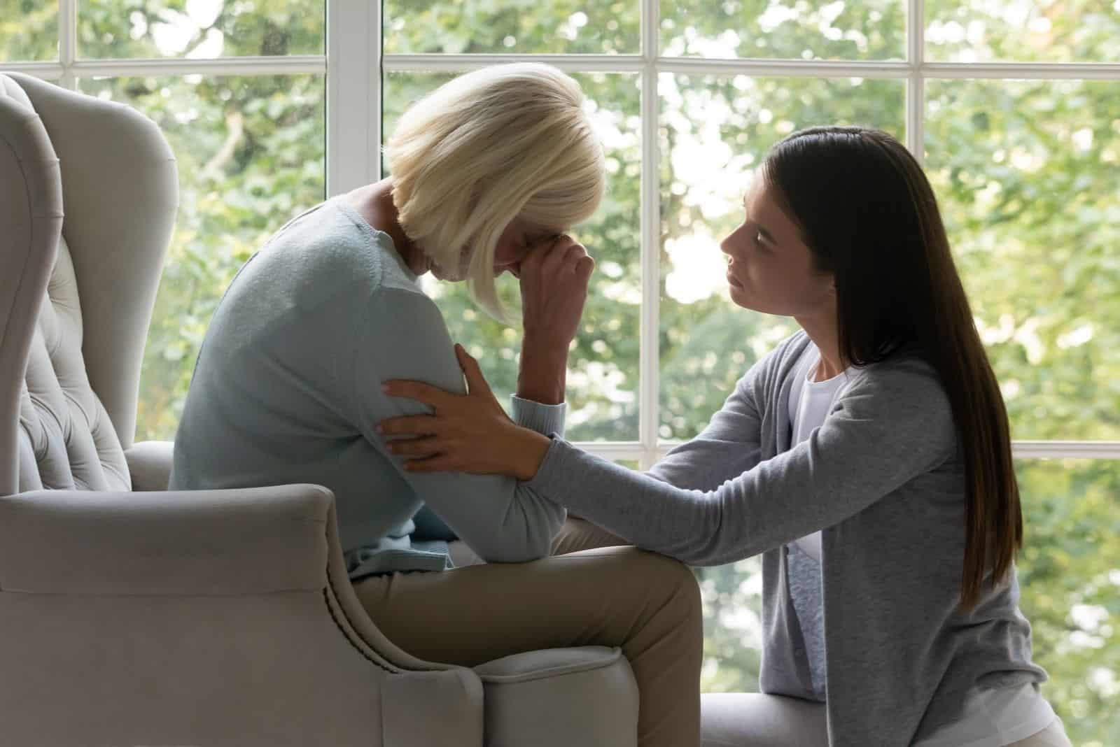 empathische tausendjährige Frau beruhigende weinende reife frau