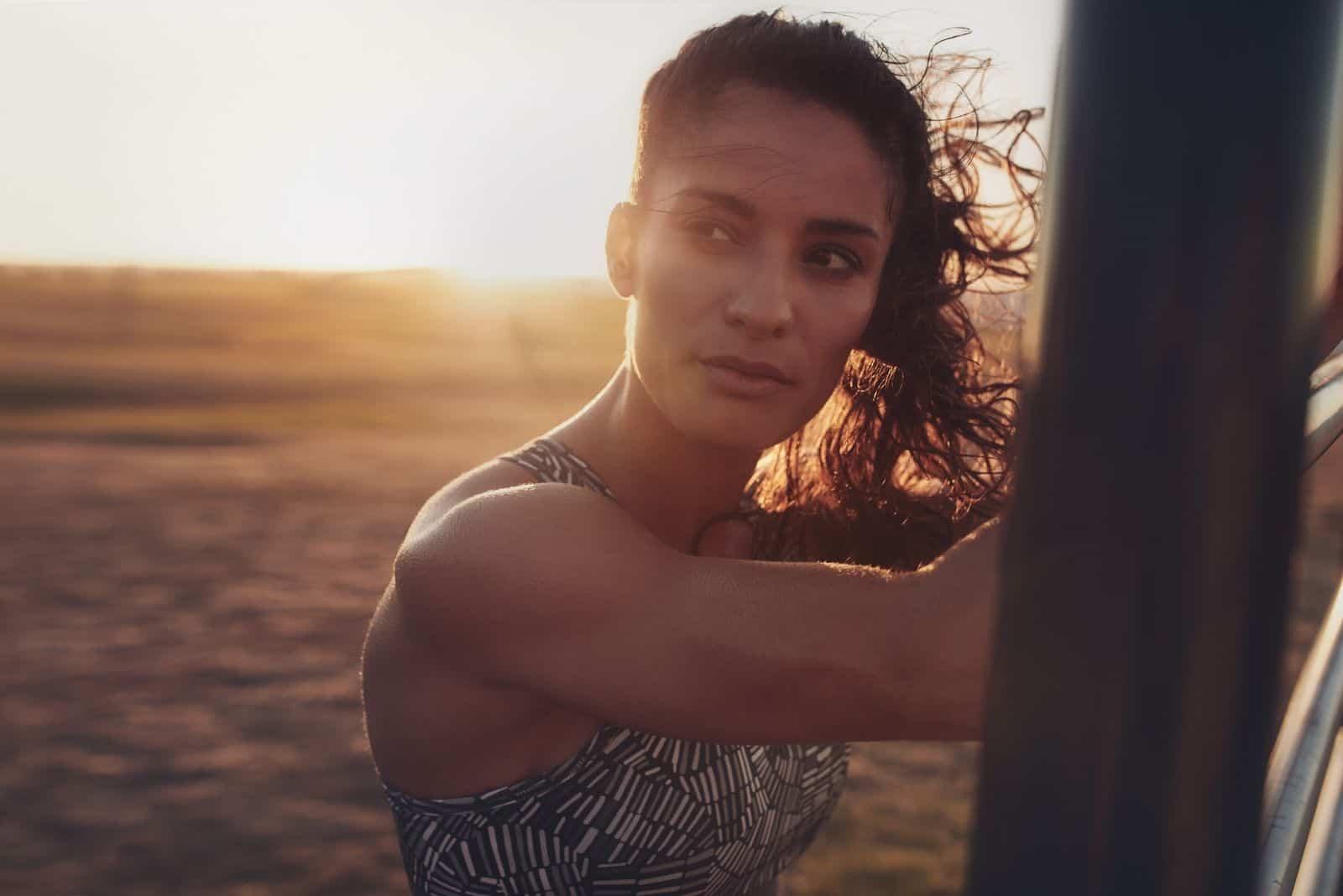 entschlossene junge Frau am Strand stehen und abends wegschauen