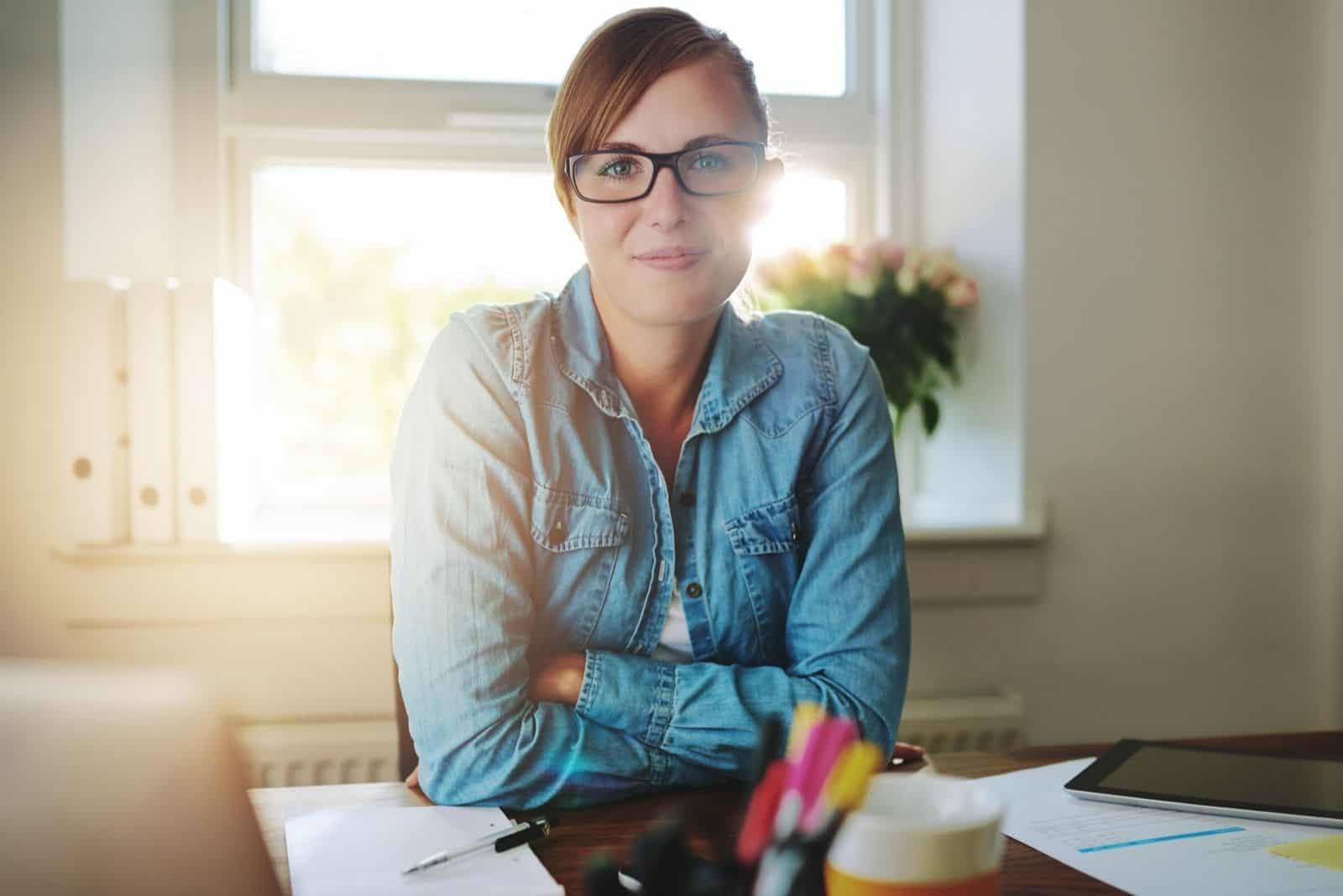 erfolgreiche Geschäftsfrau sitzt an ihrem Schreibtisch und schaut in die Kamera