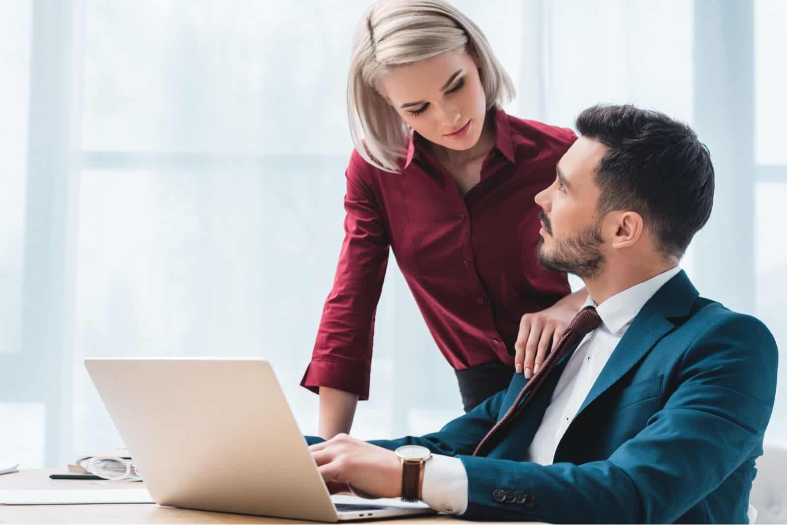 frau bürokollegin flirtet über den männlichen Bürokollegen im Büro