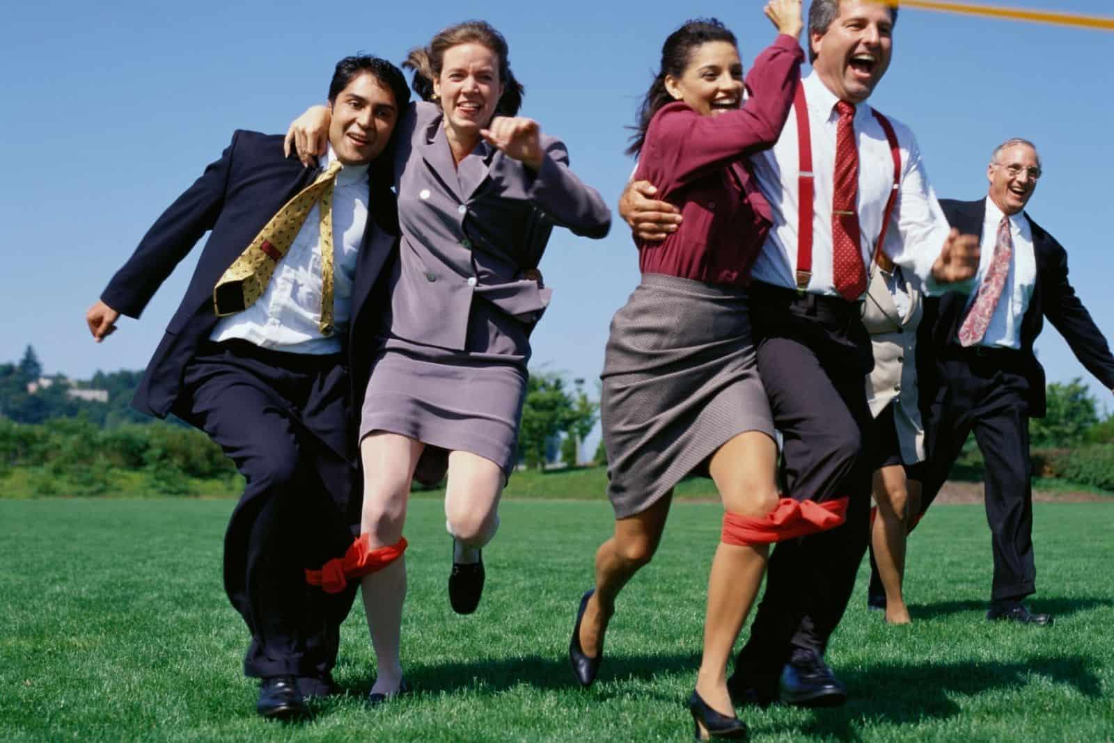 fröhliche Geschäftsleute Dreibeiniges Rennen im Freien spielen