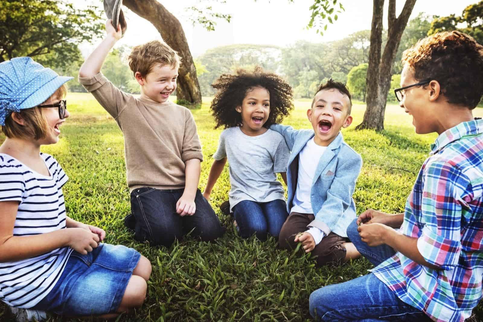 fröhliche spielende Kinder draußen auf dem boden sitzen